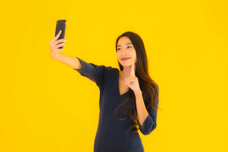 Portrait beautiful young asian woman with smart mobile phone or cellphone on yellow isolated background Фото со стока