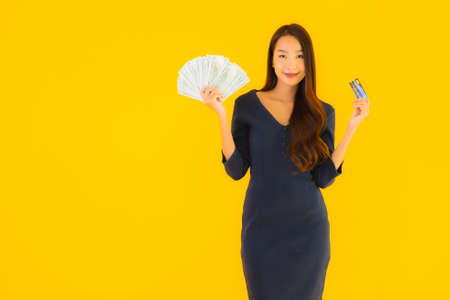 Portrait beautiful young asian woman with cash and credit card on yellow isolated background Фото со стока