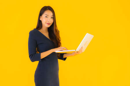 Portrait beautiful young asian woman with laptop or computer on yellow isolated background Фото со стока