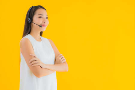 Portrait beautiful young asian woman callcenter for assistance on yellow isolated background