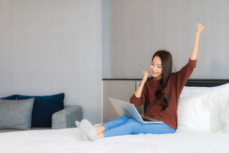 Portrait beautiful young asian woman use smart mobile phone on bed in bedroom interior Imagens