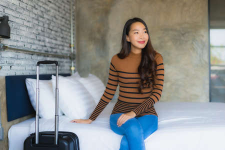 Young asian woman with luggage bag in bedroom interior
