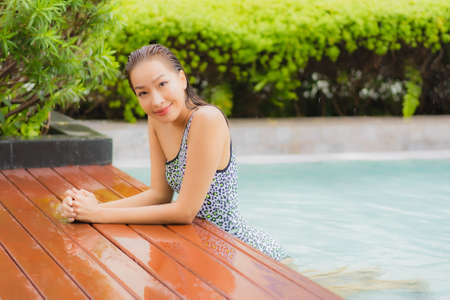 Portrait beautiful young asian woman relax happy smile around outdoor swimming pool in hotel resort for leisure vacation