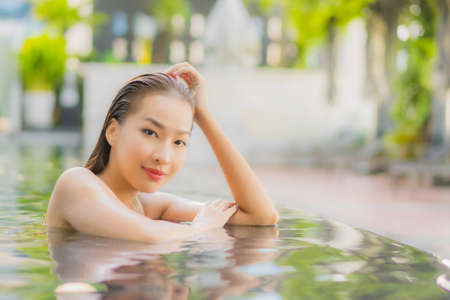 Portrait beautiful young asian woman read book around swimming pool in hotel resort for travel vacation