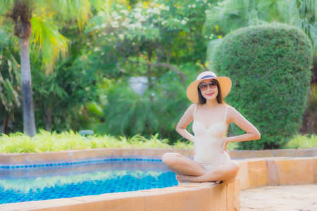 Portrait beautiful young asian woman happy smile relax around outdoor swimming pool in hotel resort for leisure vacation