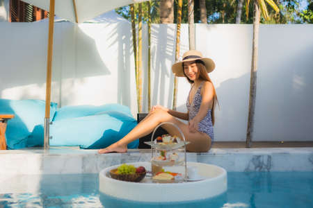 Beautiful portrait young asian woman with afternnoon tea set with coffee sit on chair around swimming pool in hotel resort