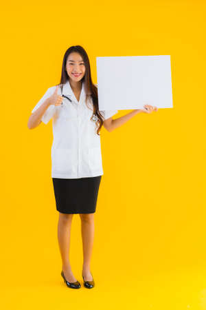 Portrait beautiful young asian doctor woman with empty white board on yellow isolated background Imagens
