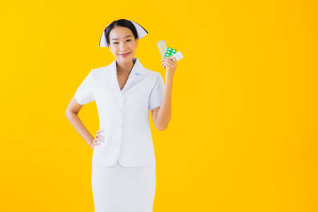 Portrait beautiful young asian woman thai nurse with pill or drug on yellow isolated background