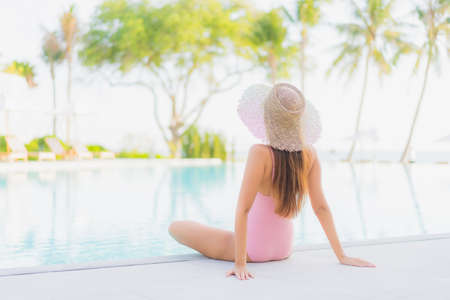 Portrait beautiful young asian woman relax leisure around outdoor swimming pool with sea beach ocean view in vacation travel