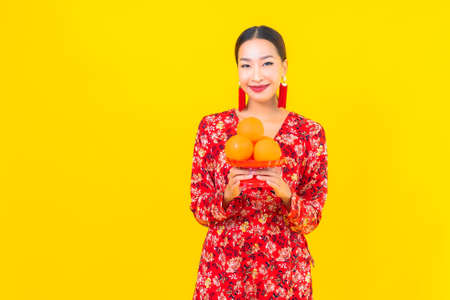 Portrait beautiful young asian woman with red envelopes on yellow background