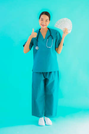 Portrait beautiful young asian doctor woman show money and cash on blue isolated background Imagens