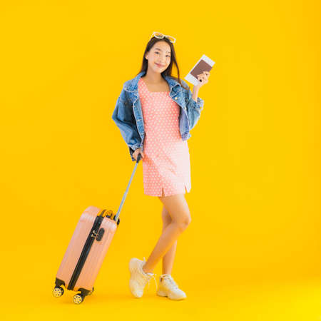 Portrait beautiful young asian woman with travel luggage passport and boarding pass on yellow isolated background