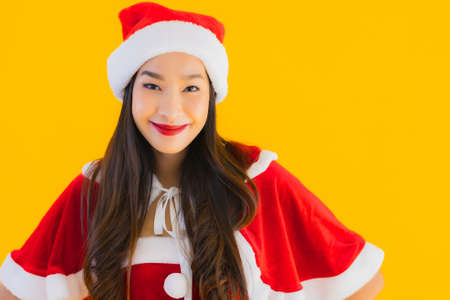 Portrait beautiful young asian woman christmas clothes and hat smile happy with other action on yellow isolated background
