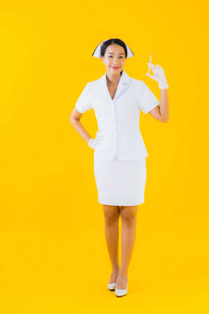 Portrait beautiful young asian woman thai nurse wear glove on yellow isolated background
