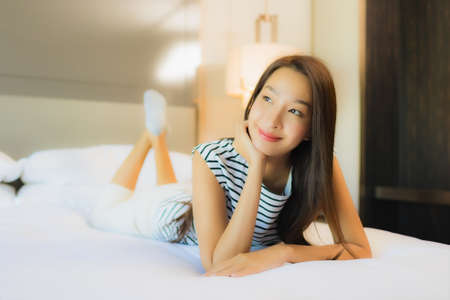 Portrait beautiful young asian woman relax smile on bed in bedroom interior