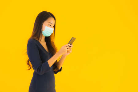 Portrait beautiful young asian woman with mask and smart mobile phone or cellphone on yellow isolated background