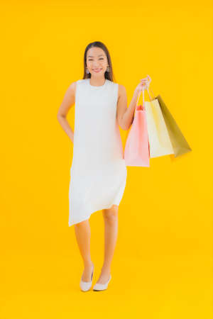 Portrait beautiful young asian business woman with shopping bag on color isolated background
