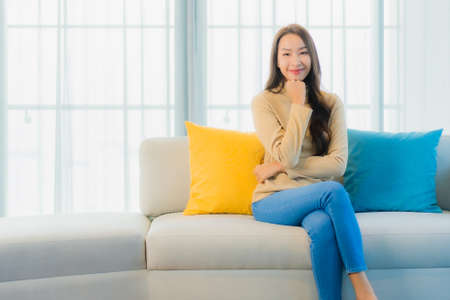 Portrait beautiful young asian woman relax leisure enjoy on sofa in living room interior area