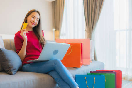 Portrait beautiful young asian woman use laptop computer with credit card for online shopping with bag on sofa