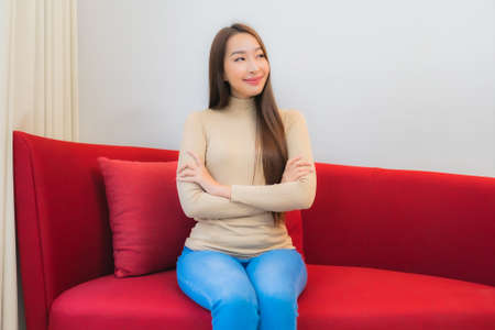 Portrait beautiful young asian woman relax smile on sofa in living room interior Imagens