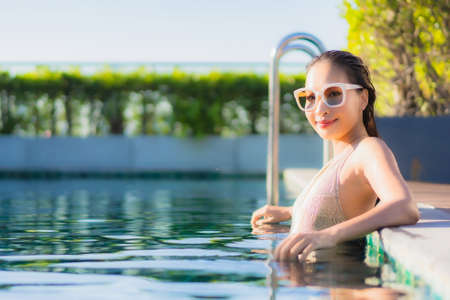 Portrait beautiful young asian woman relax smile leisure around outdoor swimming pool nearly sea beach ocean for holiday vacation