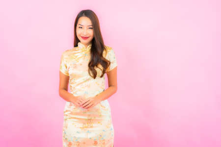 Portrait beautiful young asian woman smile in action with chinese new year concept on pink color background Imagens
