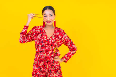 Portrait beautiful young asian woman with chopsticks on color isolated background