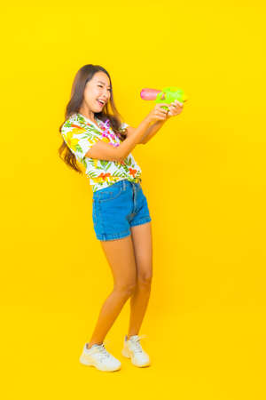 Portrait beautiful young asian woman wear colorful shirt with water gun for sonkran festival