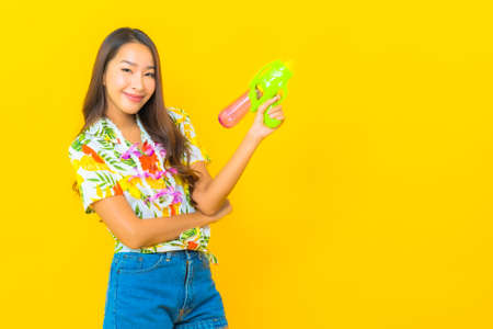 Portrait beautiful young asian woman wear colorful shirt for sonkran festival use smart mobile phone on yellow background