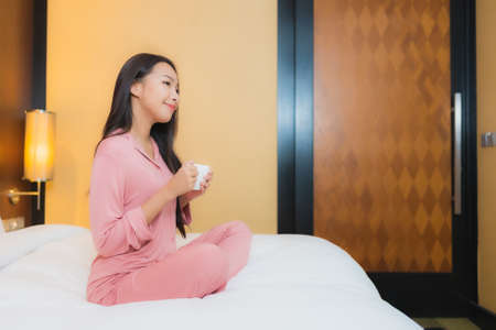 Portrait beautiful young asian woman with coffee cup on bed decoration interior of bedroom