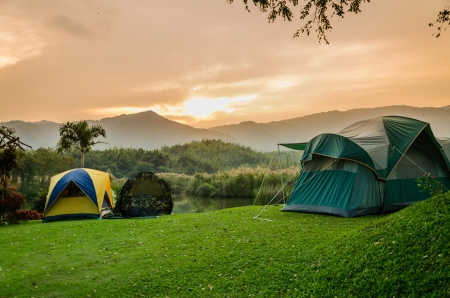 tent set on the grassland of mountain in the sunrise