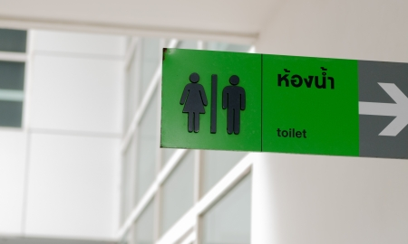 the sign of the toilet with the white building photo