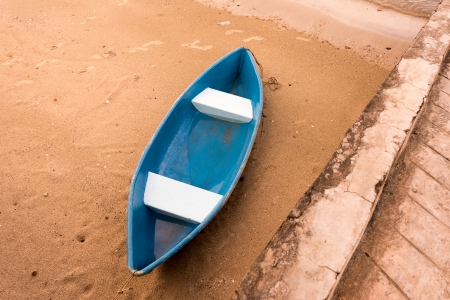 one blue boat on sand