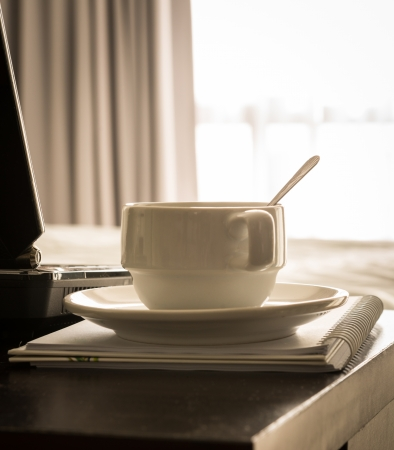 coffee cup with laptop and notebook onthe table in bed room photo