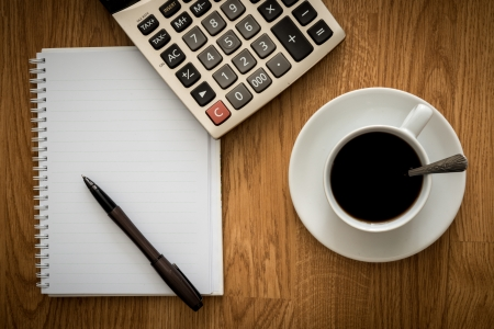 Open a blank white notebook, pen and cup of coffee and Calculator on the desk photo