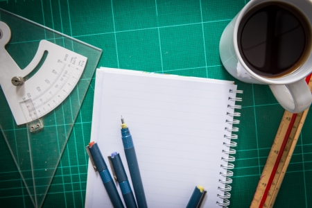 Green Cutting mats  , paper , Pen drawings , adjust angle tool , scale ruler , coffee on the wood background Stock Photo - 21125807