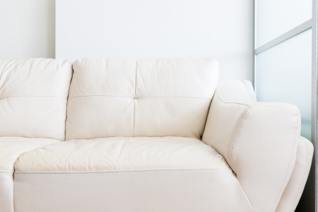 glass partition: white sofa near glass partition and white wall Stock Photo
