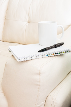 closeup coffee cup, pen, notebook is on white sofa Stock Photo
