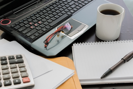 Closeup Coffee cup, laptop, Document file , pen , Calculator , notepad and glasses on wooden table Standard-Bild
