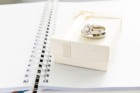 engagement ring and white gift box on note book photo