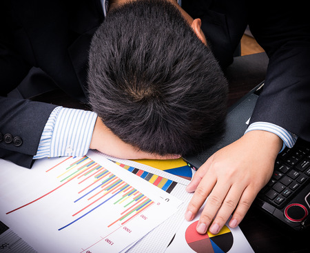 Exhausted and tired businessman sleeping in office at laptop