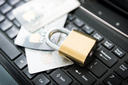 Padlock and stack of credit cards on top of laptop photo