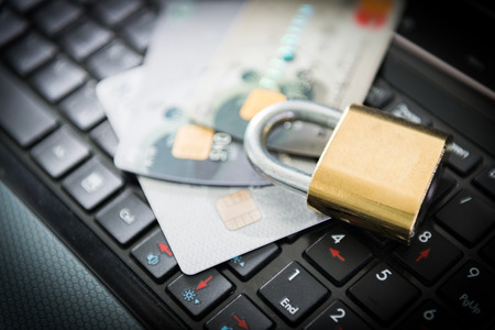Padlock and stack of credit cards on top of laptop