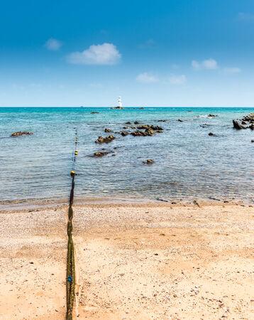 boyas: Boyas y faro blanco sobre la piedra y el mar