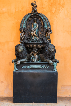 bronz: fairy and lion statues orange wall
