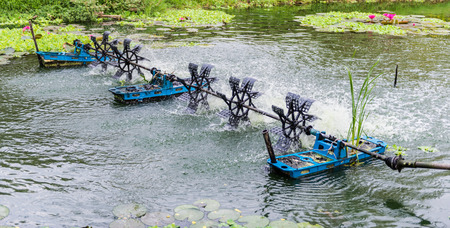a water wheel floating on the canal of park photo