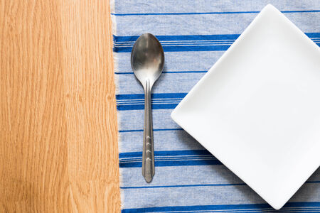 white plate and silver spoon on blue cloth. menu template photo