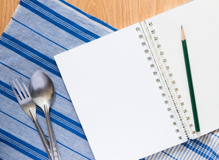 notebook , silver spoon and fork on blue cloth. menu template photo