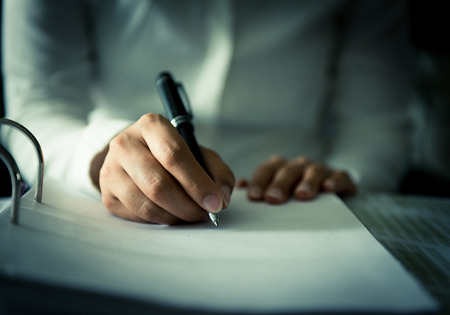 Close shot of a human hand writing something on the paper on the foreground Stock Photo