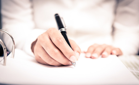 Close shot of a human hand writing something on the paper on the foreground Standard-Bild